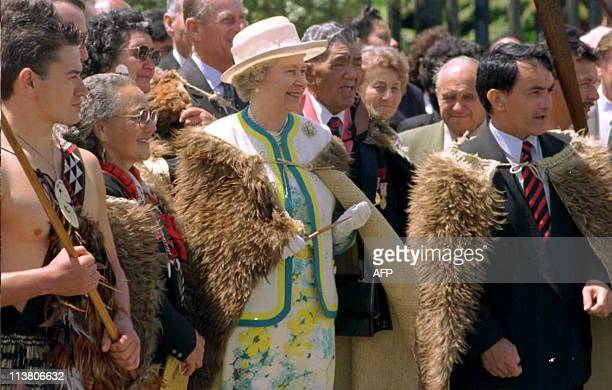 Queen Elizabeth II wearing a traditional Maori cloak of Kiwi feathers is greeted by tribal elders at the Maori Arts and Crafts Institute in...