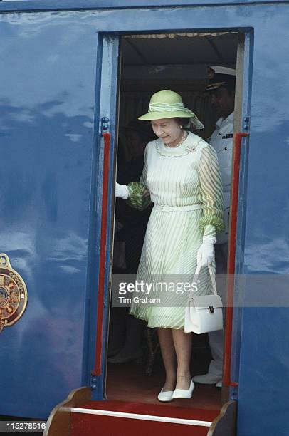 Queen Elizabeth II wearing a white dress with green trim white gloves and a green hat disembarking from the Royal train during an official visit to...