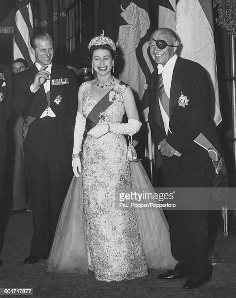 Queen Elizabeth II, wearing an evening dress and tiara, stands with Prince Philip, Duke of Edinburgh and Lewis Williams Douglas , American politician...