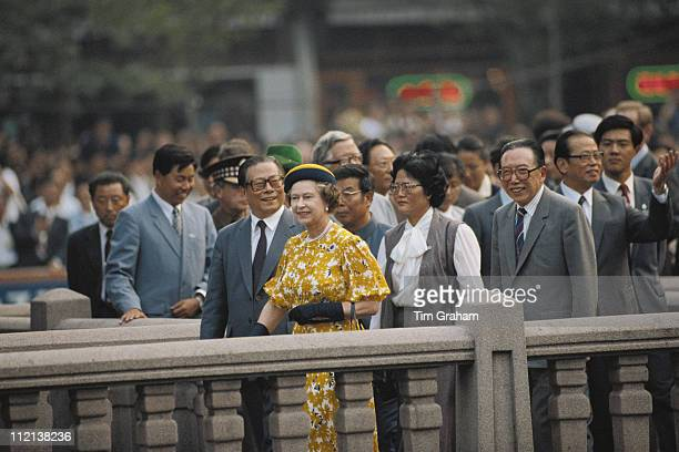 Queen Elizabeth II wearing an outfit and hat designed by fashion designer Ian Thomas on a walkabout in Shanghai during an official State Visit to...