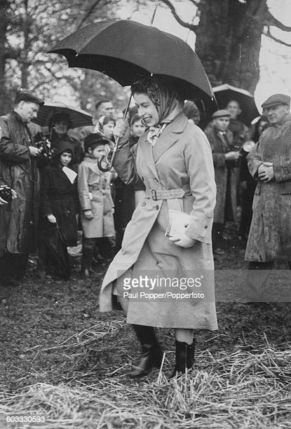 Queen Elizabeth II wearing boots and carrying an umbrella smiles as she makes her way through straw and mud at the Badminton Horse Trials in...