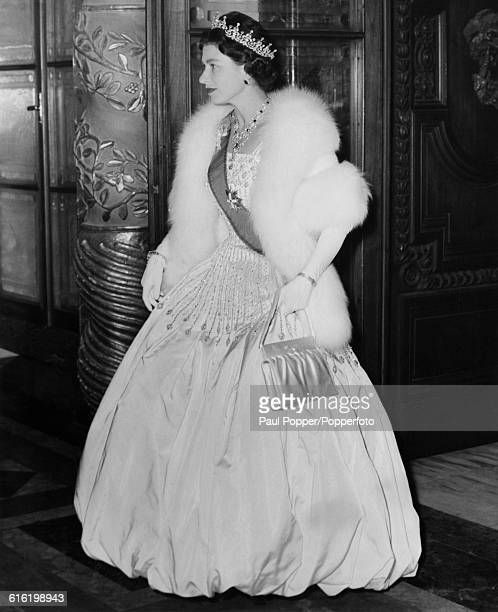 Queen Elizabeth II, wearing full evening gown along with diamond tiara and necklace, waits for the arrival of President Giovanni Gronchi of Italy for...