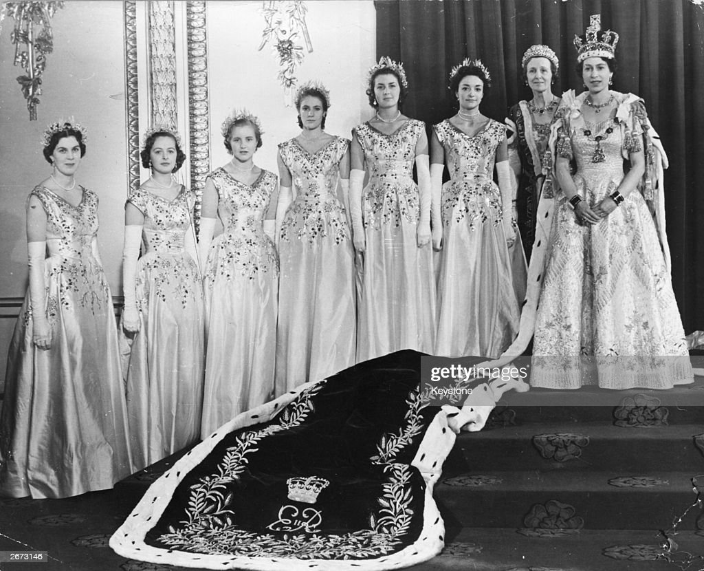 Queen Elizabeth II (right) wearing robes of state in the Throne Room at Buckingham Palace, London, on her coronation day. Her Maids of Honour are beside her: (from left to right) Lady Moyra Hamilton, Lady Jane Vane-Tempest-Stewart, Lady Anne Coke, Lady Jane Heathcote-Drummond-Willoughby, Lady Rosemary Spencer-Churchill and Lady Mary Baillie-Hamilton. Standing next to the Queen is her Mistress of the Robes, Mary Cavendish, Duchess of Devonshire.