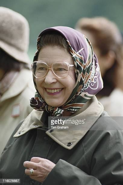 Queen Elizabeth II, wearing spectacles, a headscarf and green waxed jacket, smiling at the Royal Windsor Horse Show, held at Home Park in Windsor,...