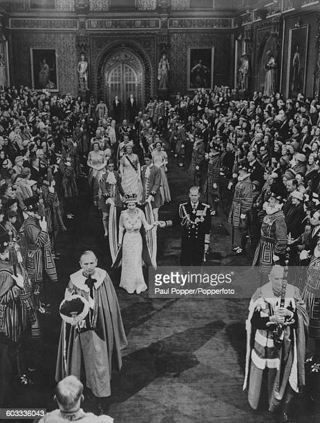 Queen Elizabeth II wearing the imperial crown and escorted by Prince Philip Duke of Edinburgh leads the state procession from the robing room through...