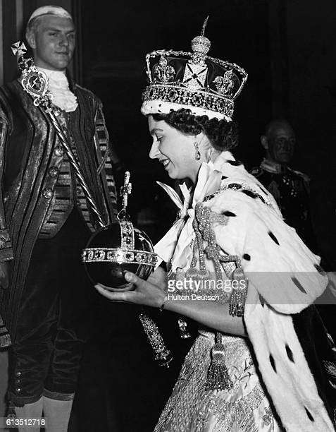 Queen Elizabeth II wearing the Imperial State Crown and carrying the Orb arrives at Buckingham Palace from Westminster Abbey after her coronation in...
