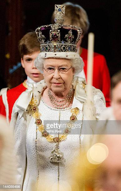 Queen Elizabeth II wearing the Imperial State Crown proceeds through the Royal Gallery in the Palace of Westminsterduring the State Opening of...