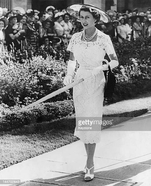Queen Elizabeth II wears a slimfitting white lace dress to a garden party in Sydney Australia before leaving for Tasmania on the liner 'SS Gothic'...