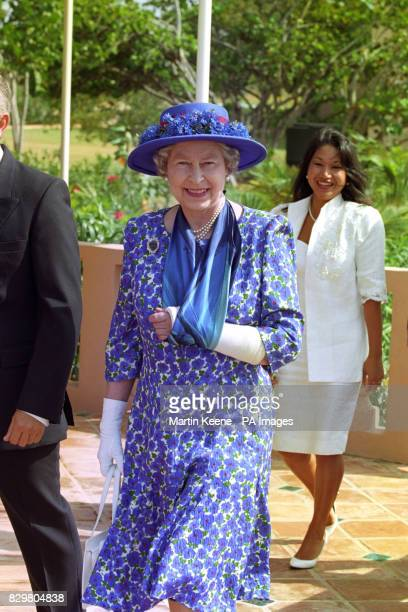 Queen Elizabeth II wears her plaster cast arm in a sling while visiting Anguilla