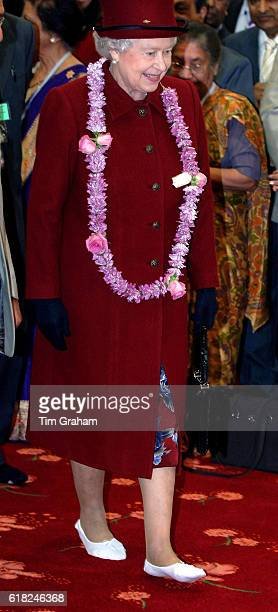 Queen Elizabeth II wears traditional slippers and a wreath during a visit to the new Bradford Hindu Temple