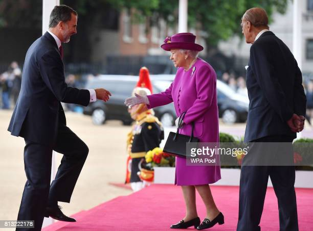 Queen Elizabeth II welcomes King Felipe VI of Spain as Prince Philip Duke of Edinburgh looks on during a welcome ceremony at the Horse Guards Parade...