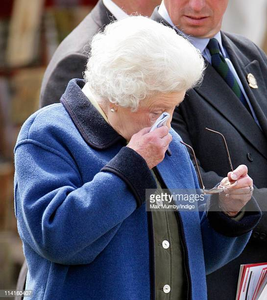 Queen Elizabeth II wipes her eyes with a handkerchief as she watches one of her horses compete at the Royal Windsor Show on May 13 2011 in Windsor...