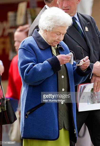 Queen Elizabeth II wipes her glasses with a handkerchief as she watches one of her horses compete at the Royal Windsor Horse Show on May 13 2011 in...