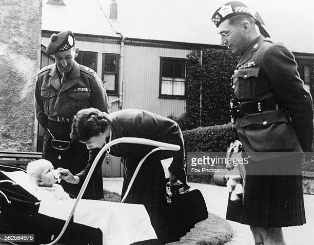 Queen Elizabeth II wiping her baby daughter Anne's face with Lieutenant Colonel J A Farmer and Lieutenant Colonel Neilson of the Argyll and...