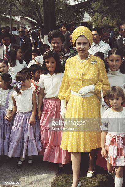 Queen Elizabeth II with a group of local children during her state visit to Mexico, 1975.
