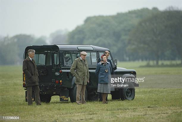 Queen Elizabeth II with Crown Equerry Lt Col Sir John Miller as well as her bodyguard and chauffeur standing by a Land Rover on the Windsor estate in...