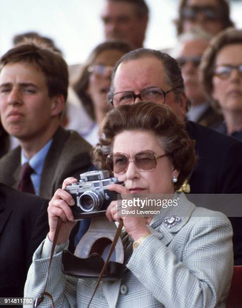 Queen Elizabeth II with her Leica camera takes a photo of Prince Philip competing in the Royal Box at the Windsor Horse Show on May 16 1982