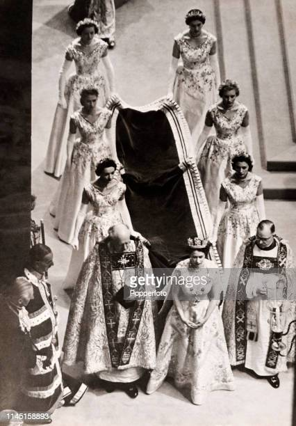 Queen Elizabeth II with her maids of honour carrying her train flanked by clergymen at her coronation in Westminster Abbey on 2nd June 1953