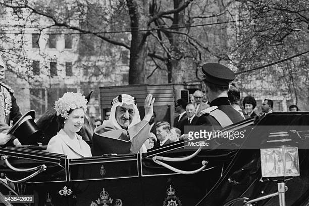 Queen Elizabeth II with King Faisal of Saudi Arabia travelling to Hyde Park for a military pageant by the King's Troop Royal Horse Artillery, London,...