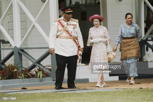 Queen Elizabeth II with King Taufa'ahau Tupou IV and Queen Halaevalu Mata'aho 'Ahome'e of Tonga outside the royal palace during her visit to Tonga...