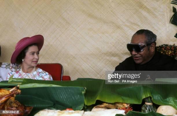 Queen Elizabeth II with King Taufa'ahau Tupou IV of Tonga at a feast at Mala'e Pangai, in the capital, Nukuʻalofa