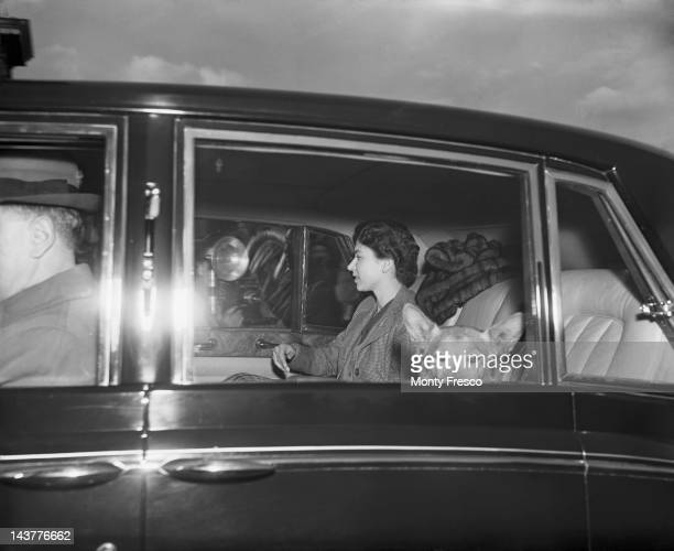 Queen Elizabeth II with one of her dogs as she arrives at Buckingham Palace in London from Windsor for Prince Charles' 7th birthday 14th November 1955