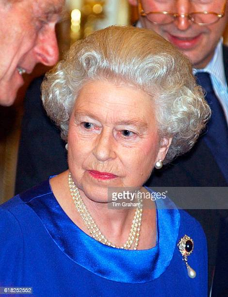 Queen Elizabeth II, with pearl necklace and sapphire and pearl brooch, pensive as she hosts a reception for serving and retired Lord-Lieutenants and...