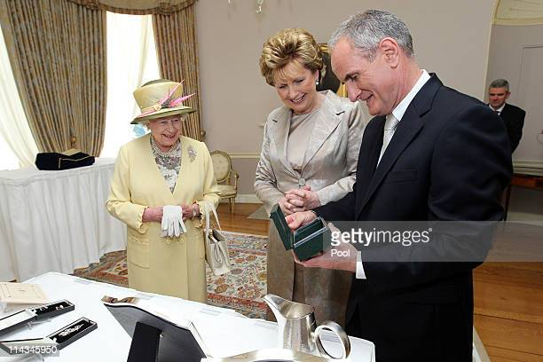 Queen Elizabeth II with President Mary McAleese and Dr. Martin McAleese at the exchange of gifts at Farmleigh on May 18, 2011 in Dublin, Ireland. The...