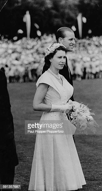 Queen Elizabeth II with Prince Philip Duke of Edinburgh beside her holds a bouquet of flowers as the royal couple attends a Government House...