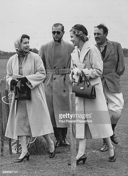 Queen Elizabeth II with Prince Philip Duke of Edinburgh walking with Weetman Pearson 3rd Viscount Cowdray and Lady Cowdray Elizabeth MatherJackson...