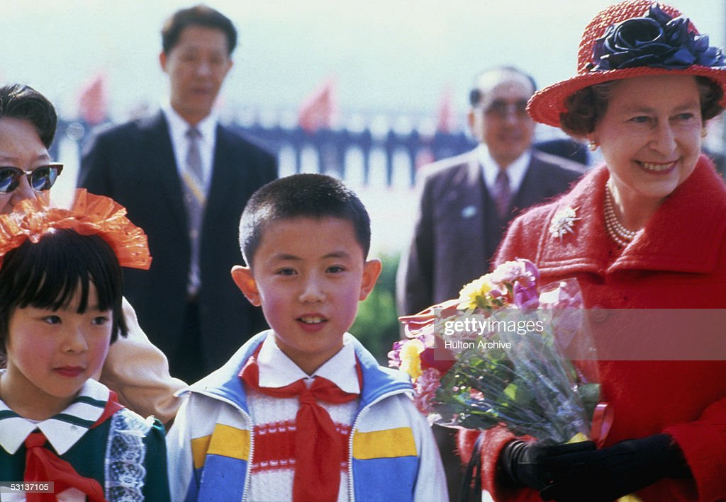 Queen Elizabeth II with school children during a tour of China, October 1986.