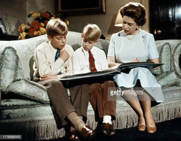 Queen Elizabeth II with two of her sons Prince Andrew and prince Edward read a book at Buckingham Palace during the recording of Queen's Christmas...