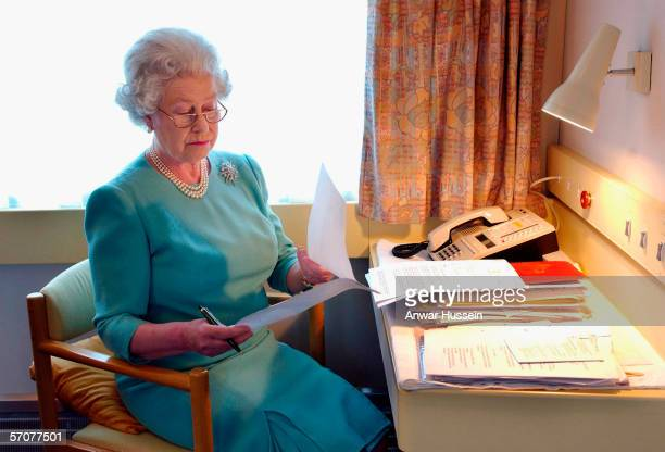 Queen Elizabeth II works at her desk on the Royal Train in May of 2002