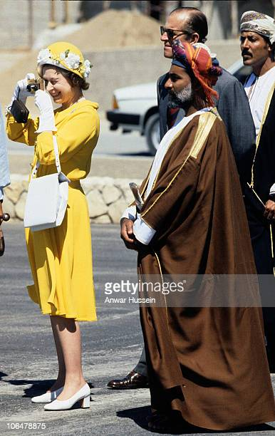 Queen Elizabeth ll accompanied by Sultan Qaboos takes photos with her golden Rollei 35 camera as she arrives with Prince Philip Duke of Edinburgh for...