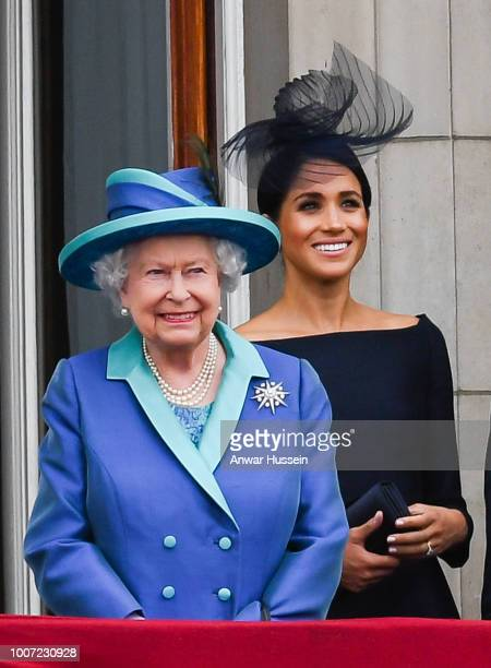 Queen Elizabeth ll and Meghan Duchess of Sussex stand on the balcony of Buckingham Palace to view a flypast to mark the centenary of the Royal Air...