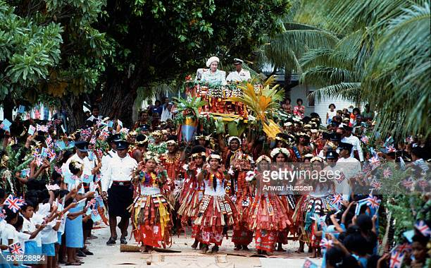 Queen Elizabeth ll and Prince Philip Duke of Edinburgh are carried in war canoes down the main street in Tuvalu during a tour of the South Pacific on...