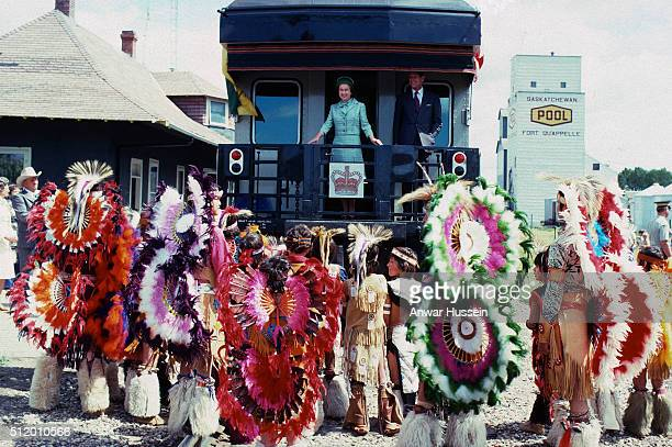 Queen Elizabeth ll and Prince Philip Duke of Edinburgh are greeted by Native Americans as they arrive by train during a tour of Canada on August 01...