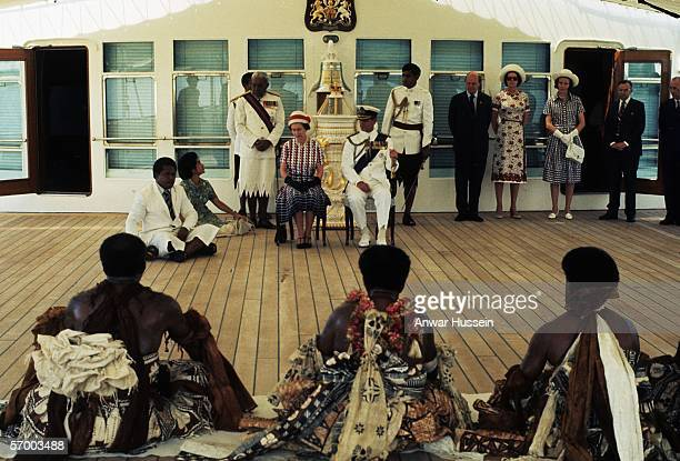Queen Elizabeth ll and Prince Philip, Duke of Edinburgh receive and are entertained by Fijian folk and traditional dancers on board the Royal Yacht...