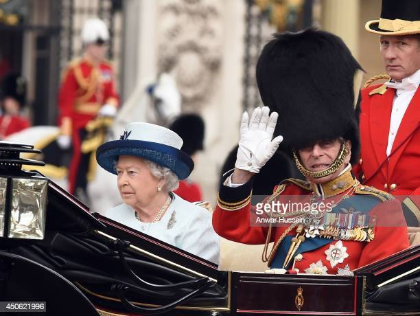 Queen Elizabeth ll and Prince Philip, Duke of Edinburgh travel in an open carriage during Trooping the Colour on June 14, 2014 in London, England.