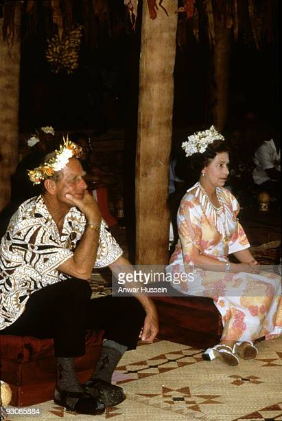 Queen Elizabeth ll and Prince Philip Duke of Edinburgh wear flowers in their hair as they attend a traditional feast in Tuvalu during their tour of...
