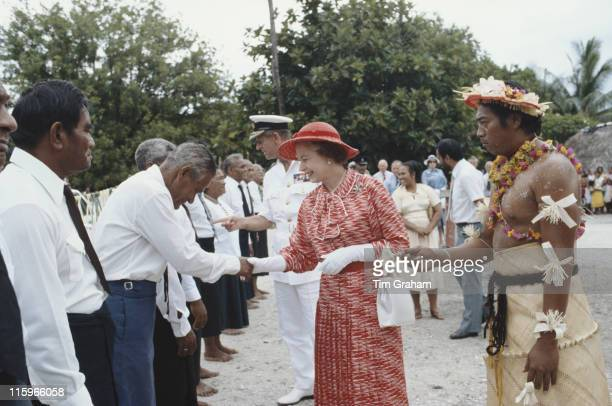 Queen Elizabeth ll and Prince Philip led by Ieremia Tabai, President of Kiribati, shaking hands as they meet local dignitaries on their arrival in...