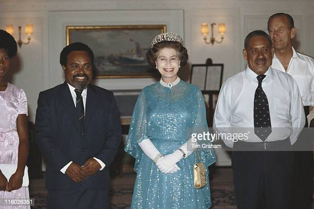 Queen Elizabeth ll and Prince Philip pose for a group portrait with guests at a reception onboard the Royal yacht Britannia moored in Papua New...