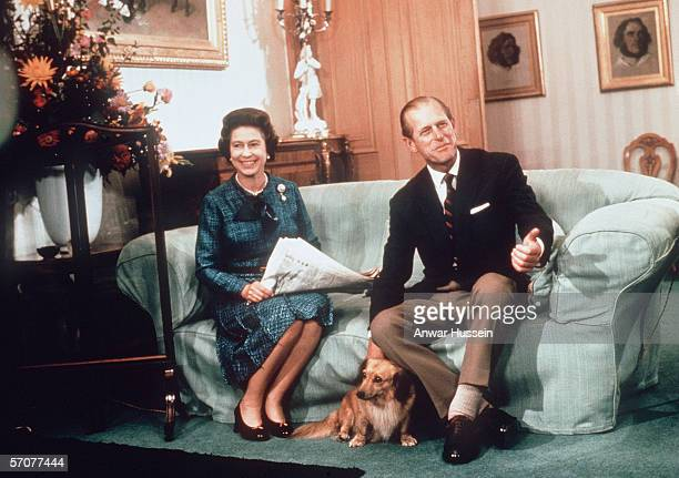 Queen Elizabeth ll and Prince Phillip the Duke of Edinburgh relaxing with their corgis and newspapers at Balmoral in 1975