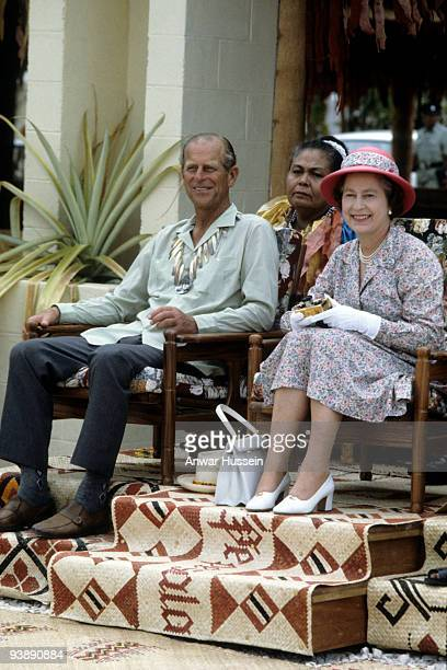 Queen Elizabeth ll holding her gold Rollei camera and Prince Philip Duke of Edinburgh wearing a traditional shell necklace watch traditional dancers...