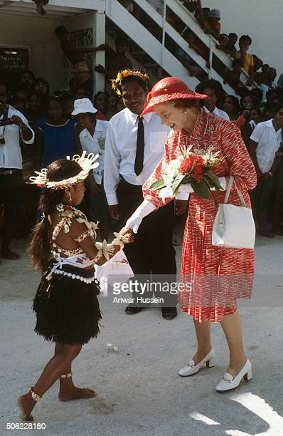 Queen Elizabeth ll is greeted by a girl in a traditional grass skirt as she arrives in Kiribati during a tour of the South Pacific on October 23 1982...