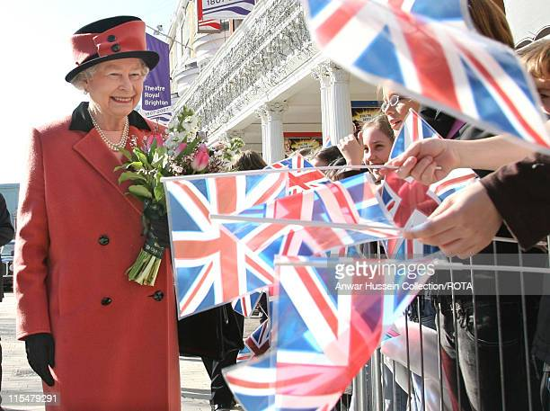 Queen Elizabeth ll is greeted by crowds waving Union Jack flags as she visits the Theatre Royal in Brighton to mark the 200th anniversary of the...