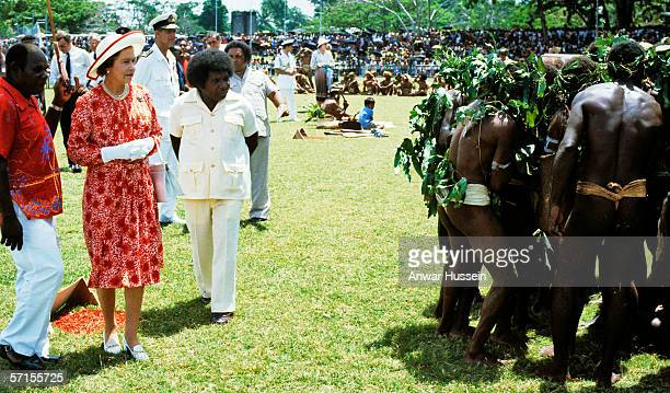Queen Elizabeth ll is is confronted by a row of bare bottoms during her visit to the Solomon Islands in the South Pacific during October of 1982