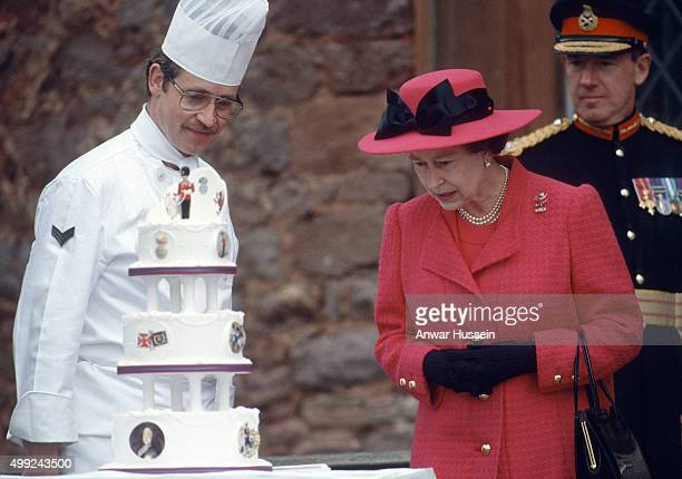 Queen Elizabeth ll is presented with a birthday cake by the men of the Royal Welch Fusiliers at Powis Castle on April 21, 1989 in Powis, Wales.