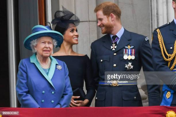 Queen Elizabeth ll, Meghan, Duchess of Sussex and Prince Harry, Duke of Sussex stand on the balcony of Buckingham Palace to view a flypast to mark...