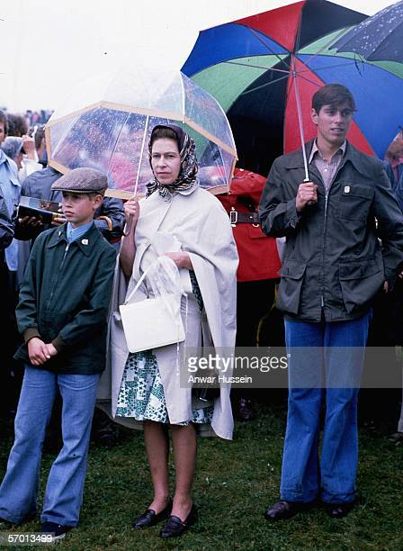Queen Elizabeth ll Prince Andrew and Prince Edward are not deterred by the rain when they attend the Olympic Games in July 1976 in Montreal Canada